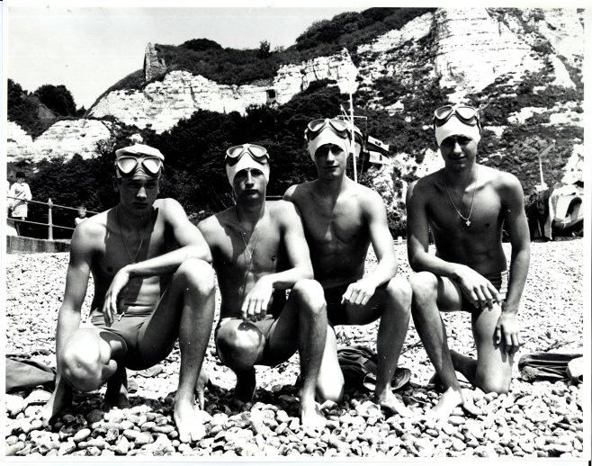 Group of Young Men Swimmers Crouched on Beach (unidentified)