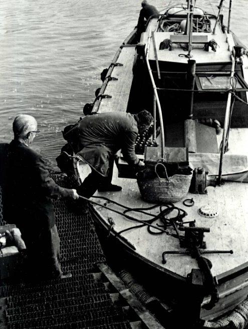 Men loading provisions aboard a boat (unidentified)