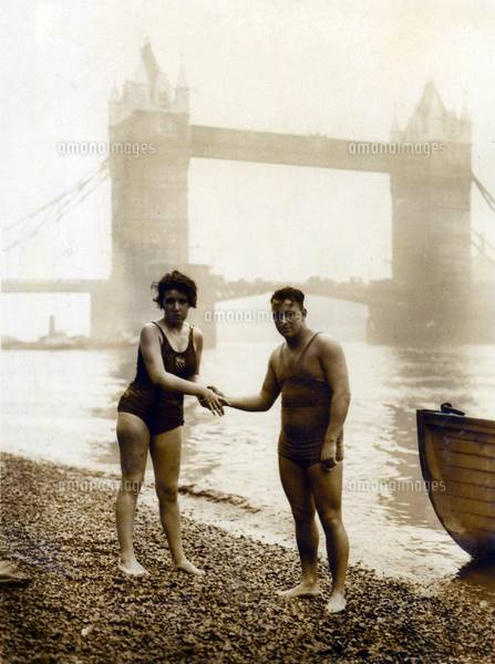 DGC308147 Agnes Nicks being congratulated by Harry Rogers at Tower Bridge, London (photo) ; photograph; Private Collection; (add. info.: shaking hands after her epic 10 mile swim from Putney; Agnes Nicks (b.1908); long distance swimming record holder and endurance swimmer; Harry Rogers swam the last 5 miles with her; in 1929 Agnes Nicks set a new record by swimming 39 miles in the river Thames in 12 hours); out of copyright